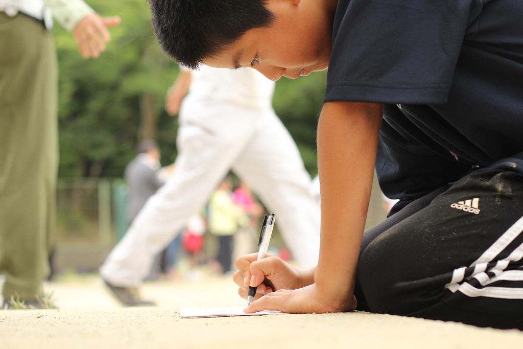 試合後、吹田一中部員に兄を持つ少年野球児が野球ノートを付けていた
